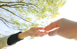 互いに指を伸ばす大人と子どもの手